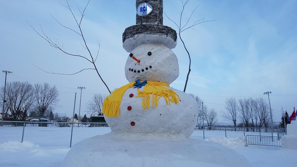 Un grand bonhomme de neige portant une écharpe et un chapeau.