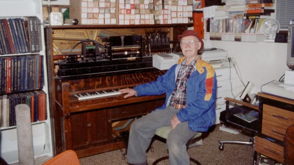 Un vieil homme assis à un piano regarde la caméra en souriant.
