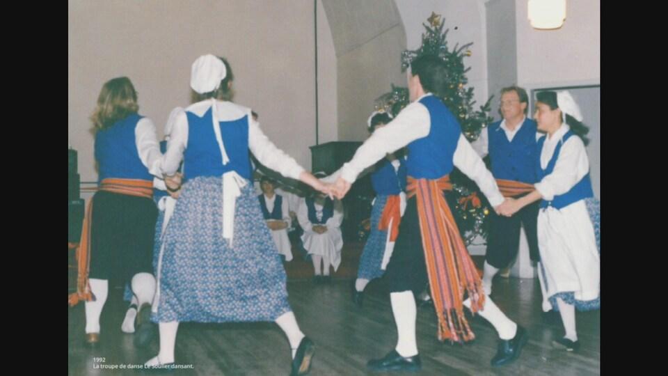 Des danseurs habillés en habit traditionnel canadien-français qui se tiennent main dans la main.