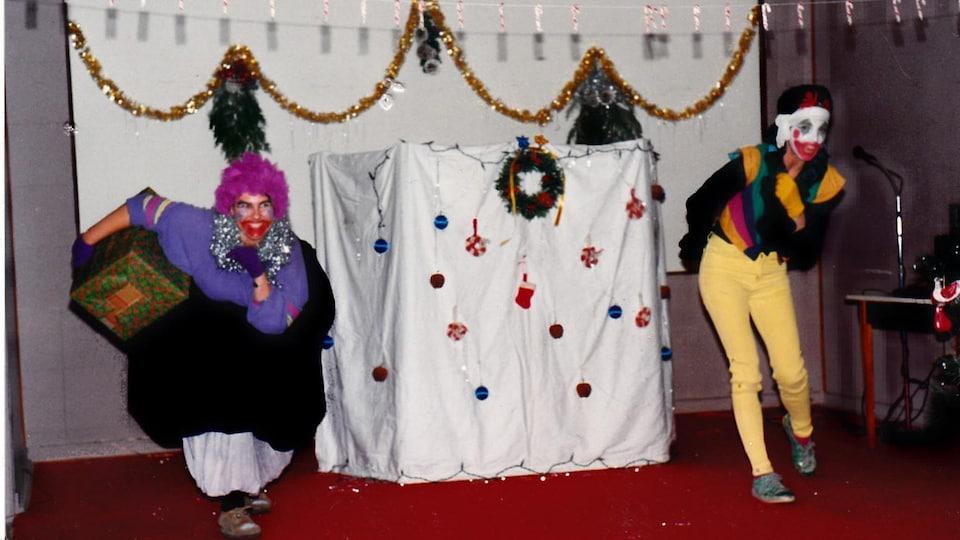 Deux personnes déguisées en clown avec un gros cadeau derrière eux.