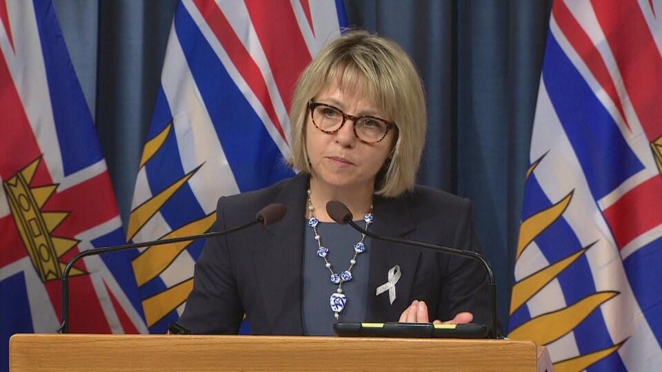 Une femme avec des lunettes derrière un lutrin parle dans un micro, des drapeaux de la Colombie-Britannique derrière elle.