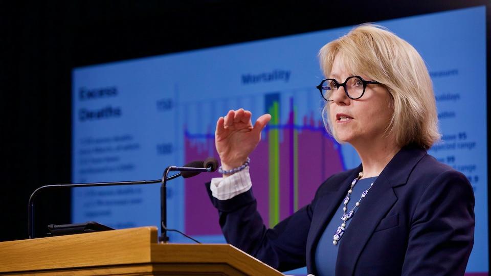La Dre Bonnie Henry se tient devant un graphique projeté sur un écran.