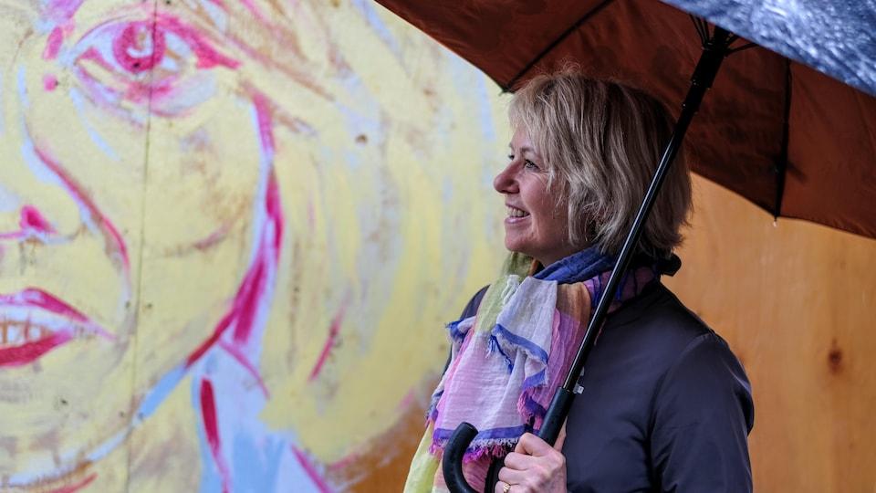 Sous un parapluie, la Dre Bonnie Henry regarde une série de peintures murales extérieures peintes par des artistes pour rendre hommage aux travailleurs de la santé dans le quartier Gastown, à Vancouver.