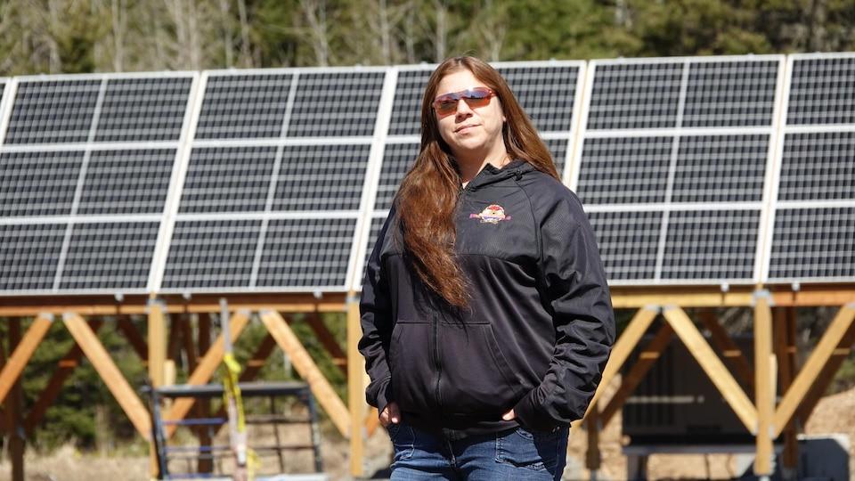 Bonnie Jerome, assistante au département de développement économique du conseil de bande de Gesgapegiag, est photographiée devant les panneaux solaires.