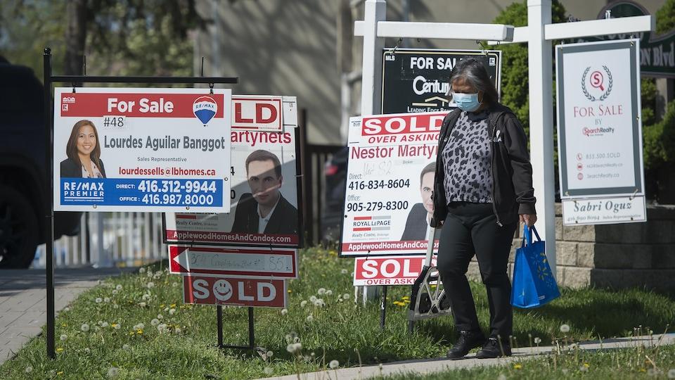 Une passante devant plusieurs panneaux de ventes immobilières.