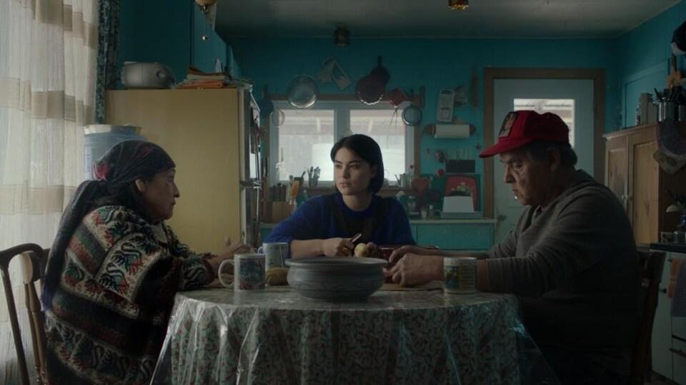 Une jeune femme épluche des pommes de terre entre deux personnes plus âgées.