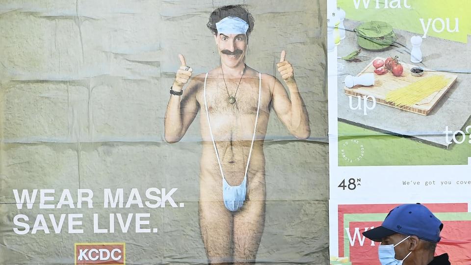 Une personne portant un masque de protection passe devant une affiche du film Borat 2, sur laquelle le personnage principal, complètement nu, porte un masque sur son front et un autre sur ses parties génitales.