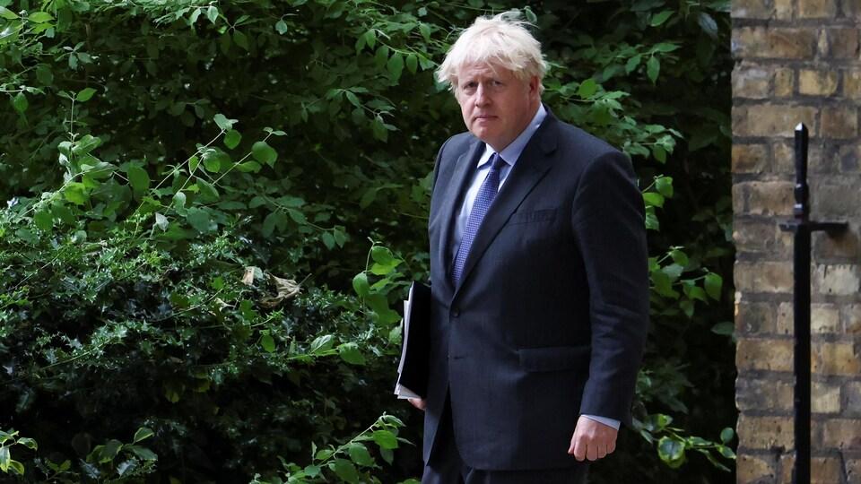 Boris Johnson marchant avec un dossier sous le bras.