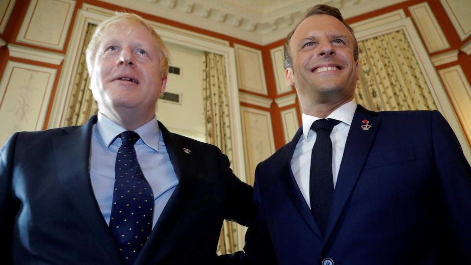 Boris Johnson et Emmanuel Macron se tiennent côte à côte.