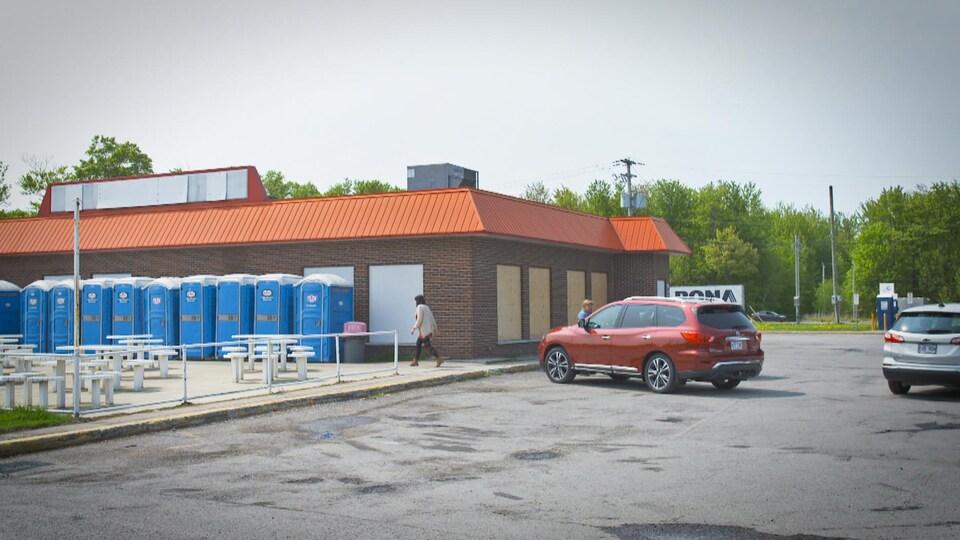Des toilettes bleues alignées sur un mur de briques.