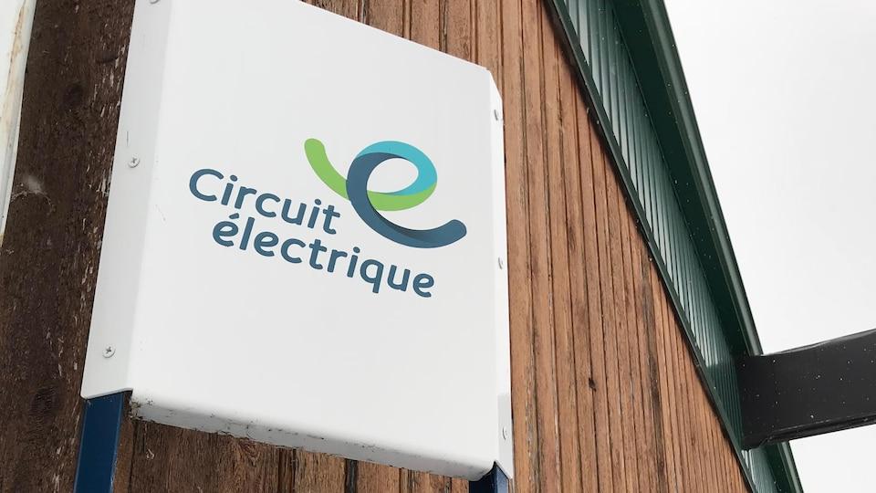 Panneau d'une borne de recharge lente pour voitures électriques avec la mention « circuit électrique » inscrite.
