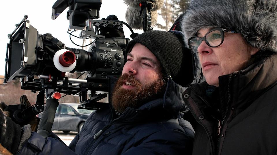 Images de Gilles qui tient une caméra de tournage et Denise qui l'écoute.