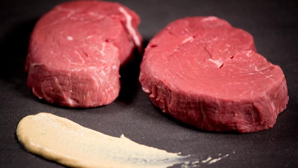 Deux morceaux de steak crus sur une planche noire.