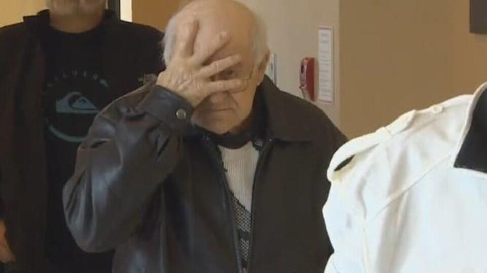 Delmore Boudreau se masque le visage d'une main en marchant dans le palais de justice