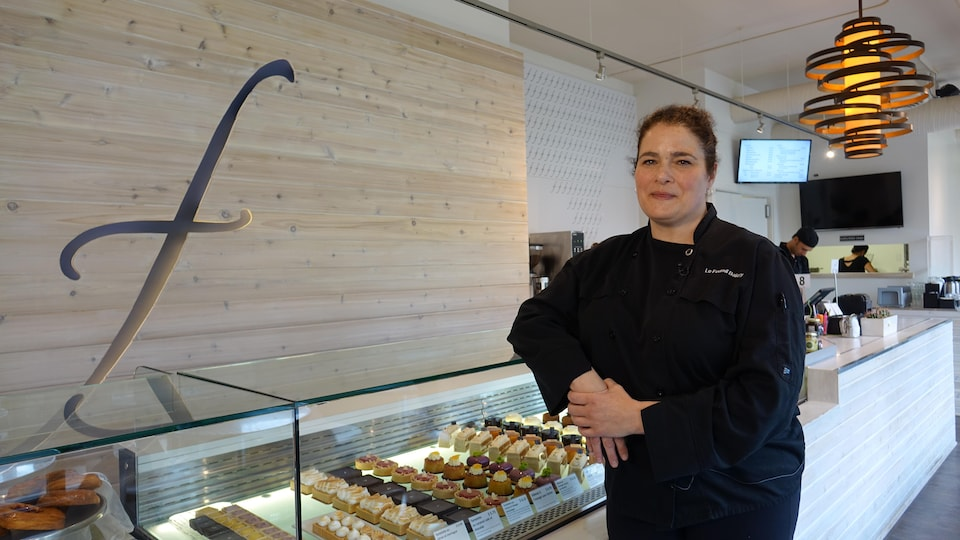 Pascale Tétreault se tient appuyée sur une vitrine remplie de pâtisseries.