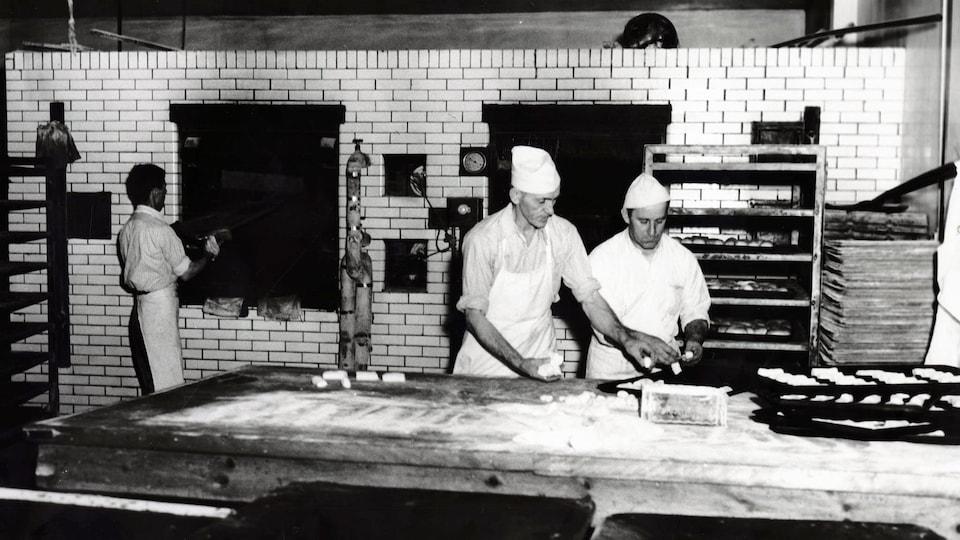 Photo en noir et blanc de boulangers qui manipulent de la pâte sur une grande table de travail avec une personne en train de mettre quelque chose au four en arrière.