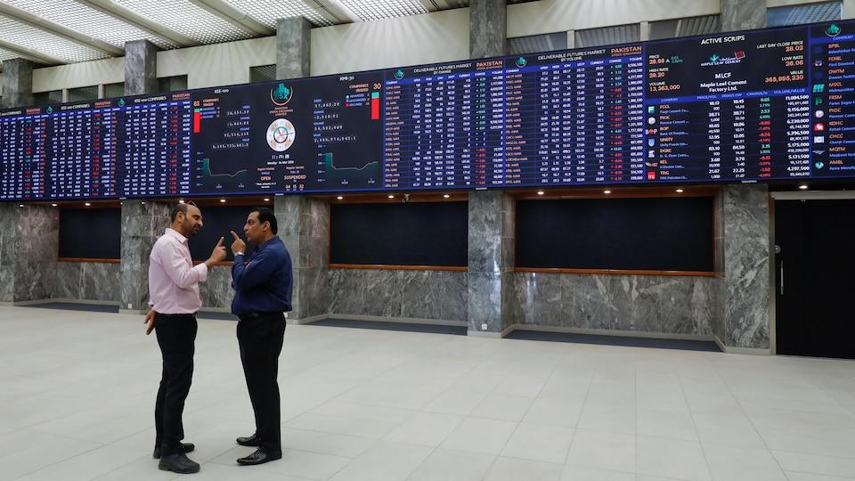 Deux hommes se tiennent debout devant des tableaux des marchés boursiers.