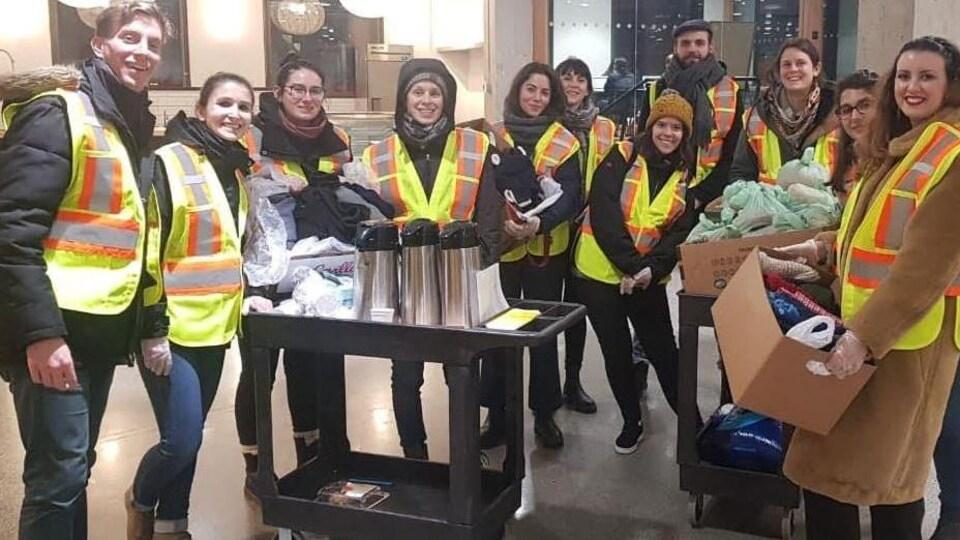 Onze personnes qui portent des manteaux chauds et des dossards jaunes posent posent pour l'appareil-photo avec dans leurs mains des boîtes en carton qui contiennent des vêtements et des sacs de nourriture et devant un chariot avec des thermos.