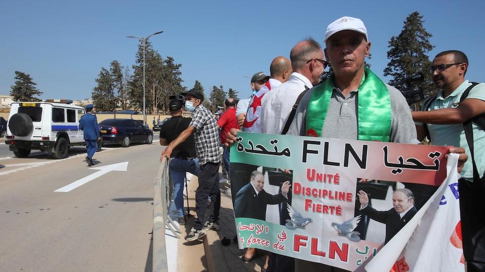 Un homme tenant une pancarte à l'effigie de Bouteflika, aux abords du cimetière.