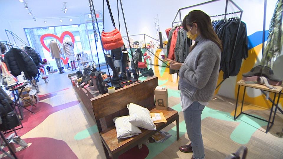 Une employée dans un magasin de vêtements, devant une pile de colis à livrer.