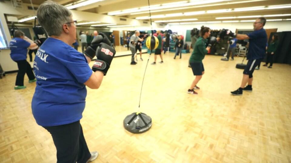Une femme, gants de boxe aux mains, s'entraîne avec d'autres personnes en arrière-plan.