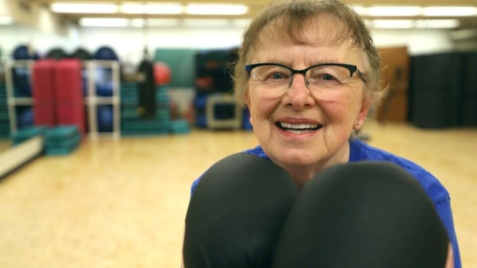 Gros plan sur le visage de Barb Bender, qui a ses gants de boxe aux mains.
