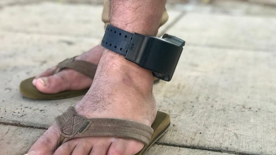 Un bracelet électronique à la cheville d'une personne.