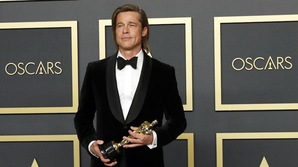 Brad Pitt tient son Oscar dans ses mains.