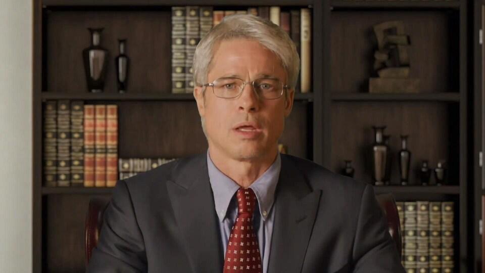 Un homme vêtu d'un veston parle à la caméra, assis devant une bibliothèque.