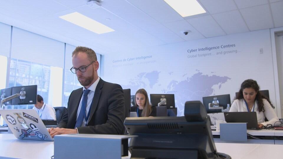 La photo montre Pierre-Alexandre Braeken et trois de ses collègues assis devant leur ordinateur au Centre de cyberintelligence de Deloitte