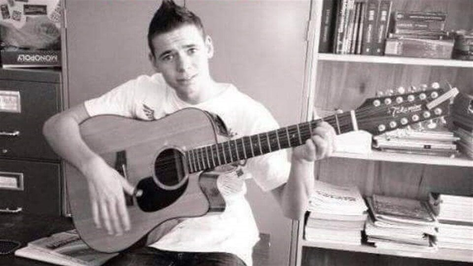 Un jeune homme qui joue de la guitare.
