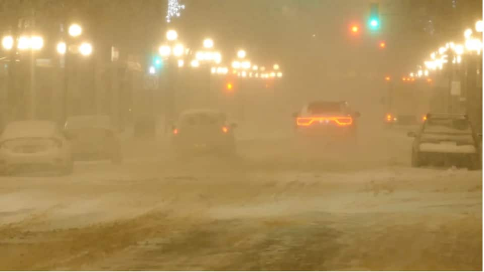 Des voitures roulent dans le blizzard.