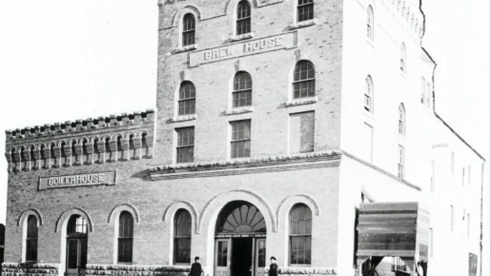 Photo en noir et blanc d'un bâtiment carré de brique, portant l'inscription «Brew House».