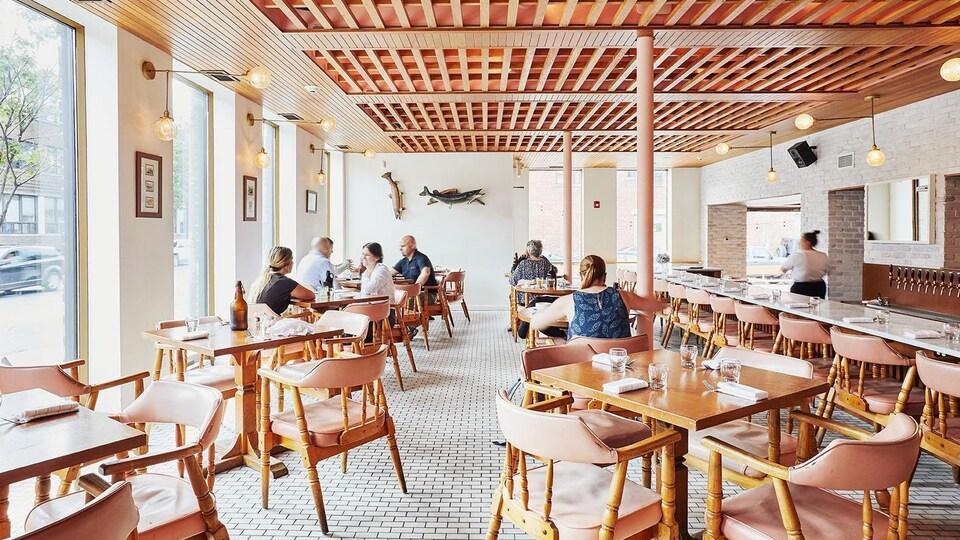 Des gens sont assis à des tables à l'intérieur d'une grande salle avec un long comptoir en plein jour dans la brasserie.