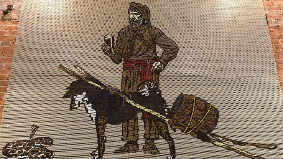 Une oeuvre d'arts démontre un homme, du temps des explorateurs, avec une bière en main et un chien qui transporte un baril de bière.