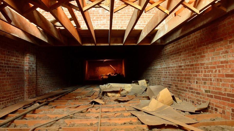 Une pièce en rénovation où l'on voit des poutres et de la mousse isolante.