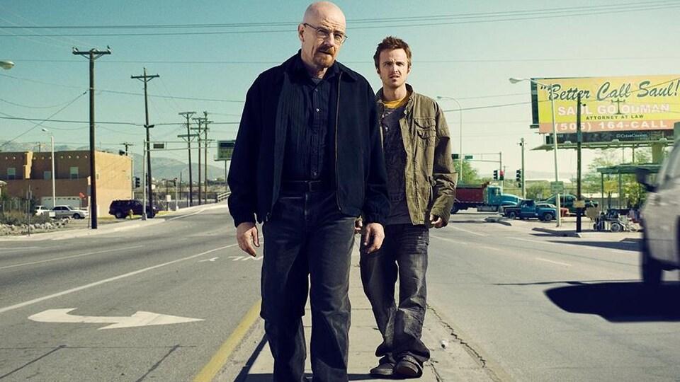 Les deux hommes se tiennent au milieu d'une rue, éblouis par le soleil.