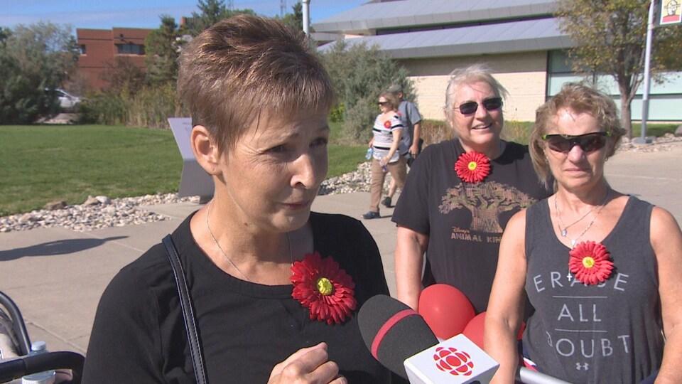 Une femme portant une fleur rouge sur son chandail en entrevue avec Radio-Canada.