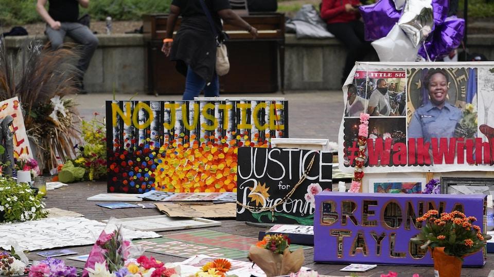 Des gerbes de fleurs sont déposées devant des pancartes où on peut par exemple lire « Justice pour Breonna » ou « Pas de justice ».