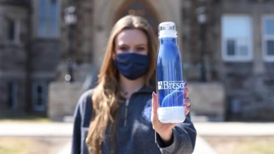 Une étudiante tient une bouteille d'eau réutilisable sur laquelle il est inscrit Brescia University College.