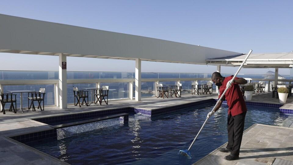 Un homme nettoie une piscine.