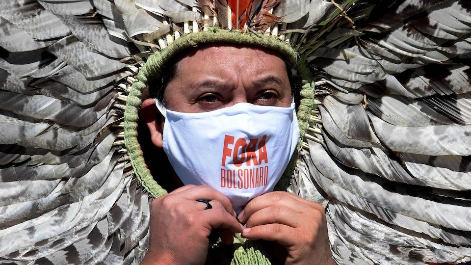 Un homme portant un masque et une coiffe traditionnelle de plumes porte un masque sur lequel on peut lire « Dehors Bolsonaro ».