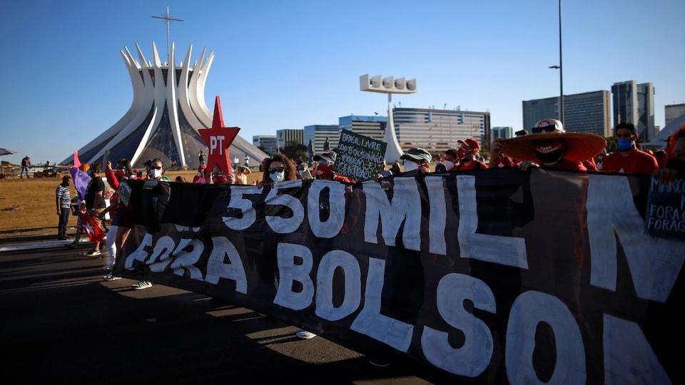 Une large bannière dénonçant le président Bolsonaro dans le décor de Brasilia.