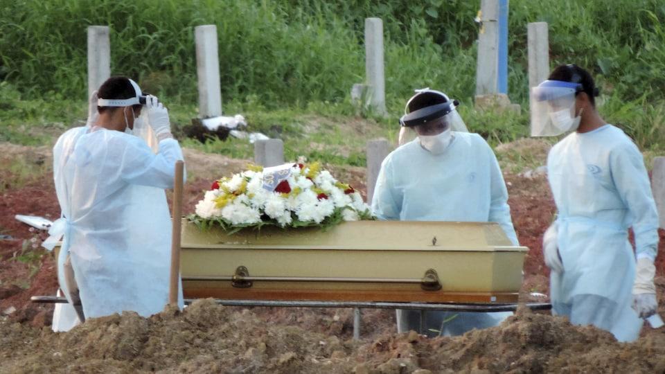 Des employés mettent un cercueil en terre.