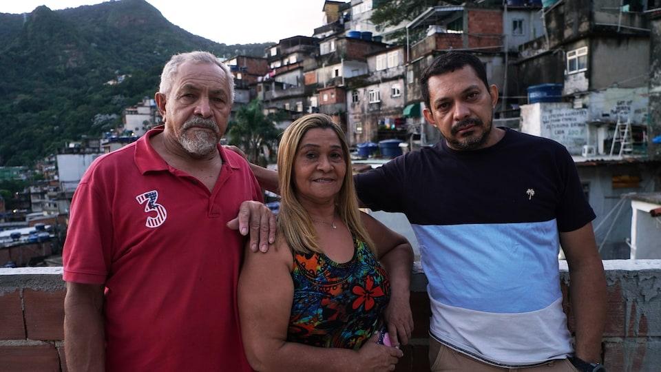 Trois personnes posent devant une colline.