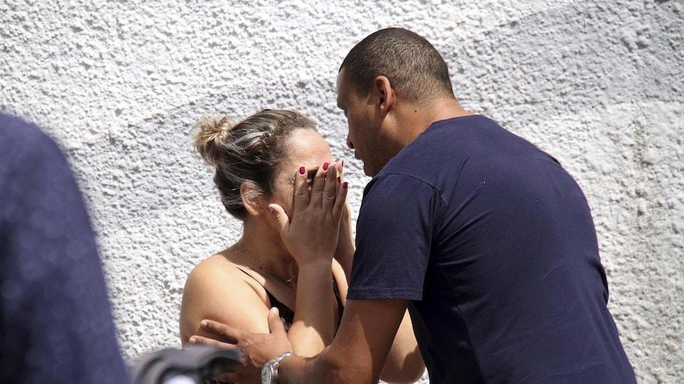 Un homme pose ses mains sur les bras d'une femme qui cache son visage dans ses mains.
