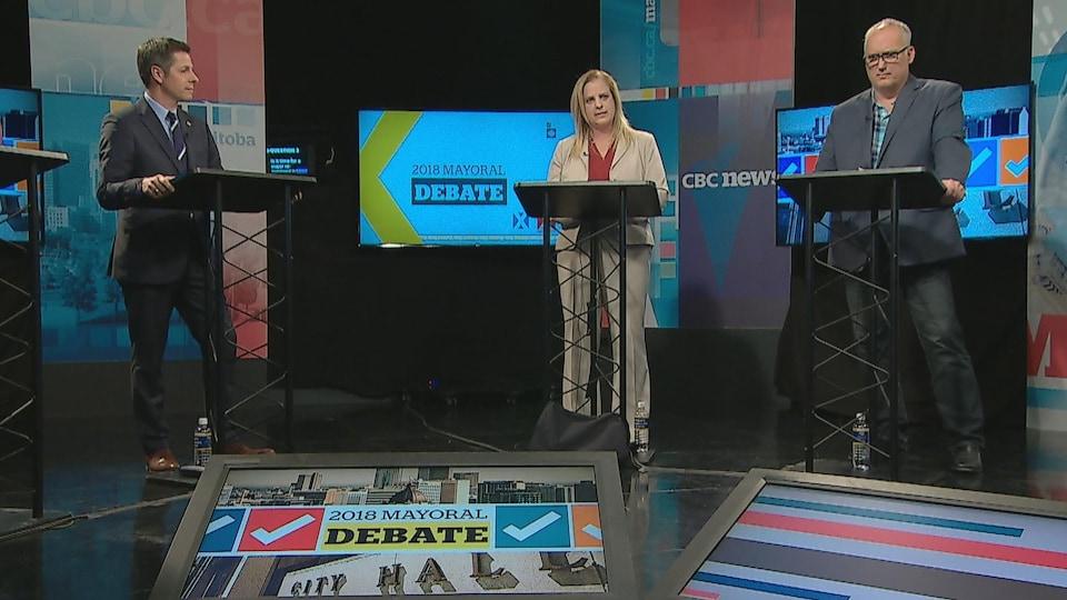 Les trois candidats derrière des lutrins, dans un studio de télévision.