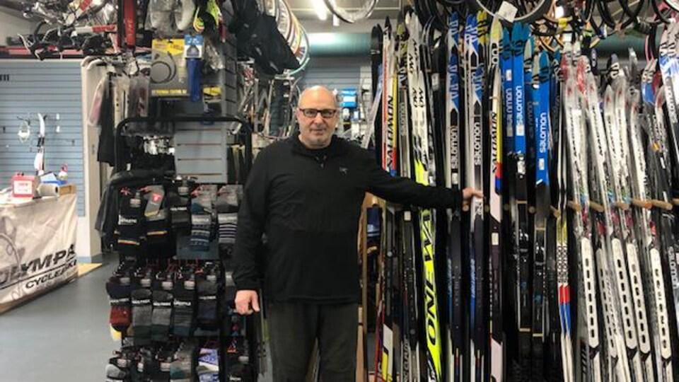 Brian Burke dans son commerce face à une rangée de skis et sous des vélos suspendus au plafond.