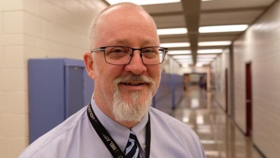 Un homme blanc porte une barbe blanche et une chemise bleu dans un couloir d'école.