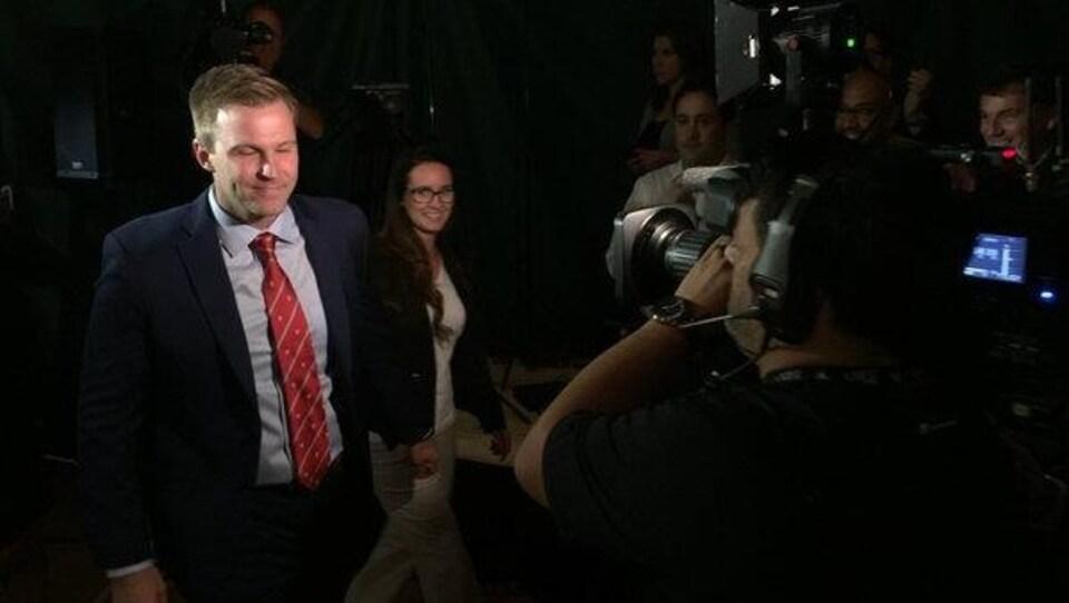 Brian Gallant s'avance devant des journalistes.